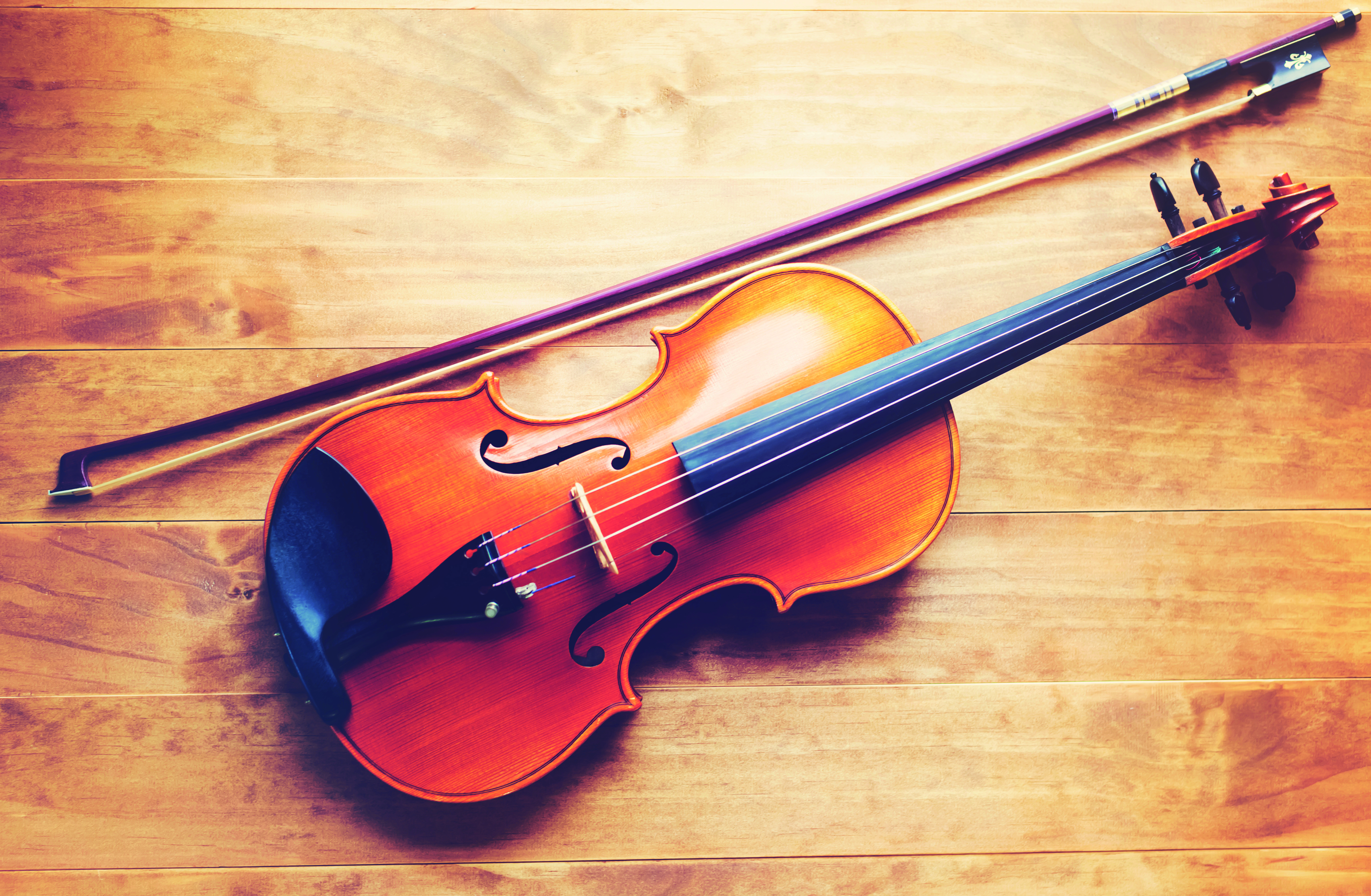 Violin and bow lying on a wooden textured table